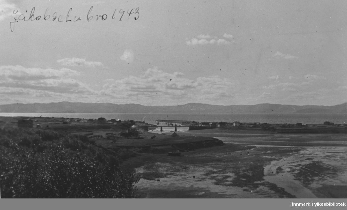 Oversiktsbilde tatt fra Vestre Jakobselv -43. Bildet er tatt fra elvekanten mot byen. Bro ligg mitt på bildet. Bakerst fjorden og fjellene på andre siden. Det er sommer og dagen er solig.