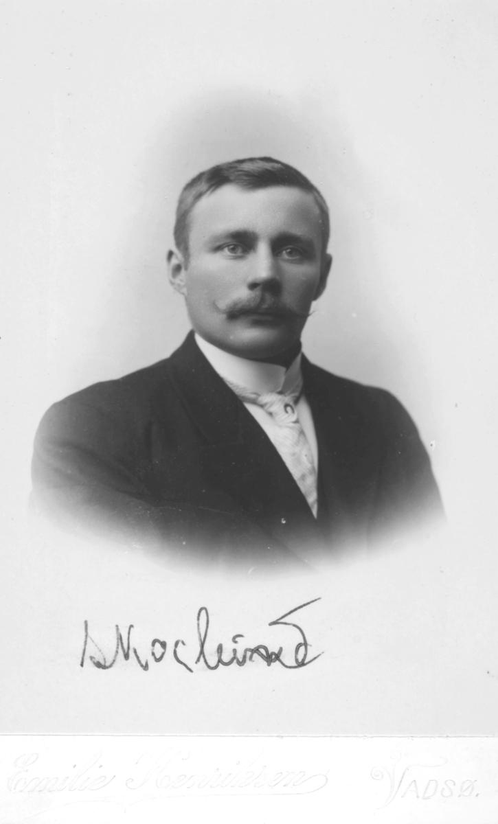 Halvfigur portrett av en mann med bart, ikke identifisert. Han er kledd i dress og slips. Et navn er notert på bildet, men uleselig.