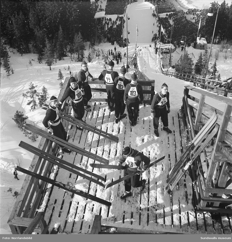 En rolig serie bilder från Svenska skidspelen 1951 i Sundsvall. Bildserien är från backhoppningen i Kubenbacken med allt från arrangörernas slit med att snöröja på åskådarplats, delvis med hjälp av häst, till domartorn och speakerplats med den tidens teknik. Vackra bilder av tävlingsplatsen i olika vinklar med idrottsmännen och den månghövdade publiken.