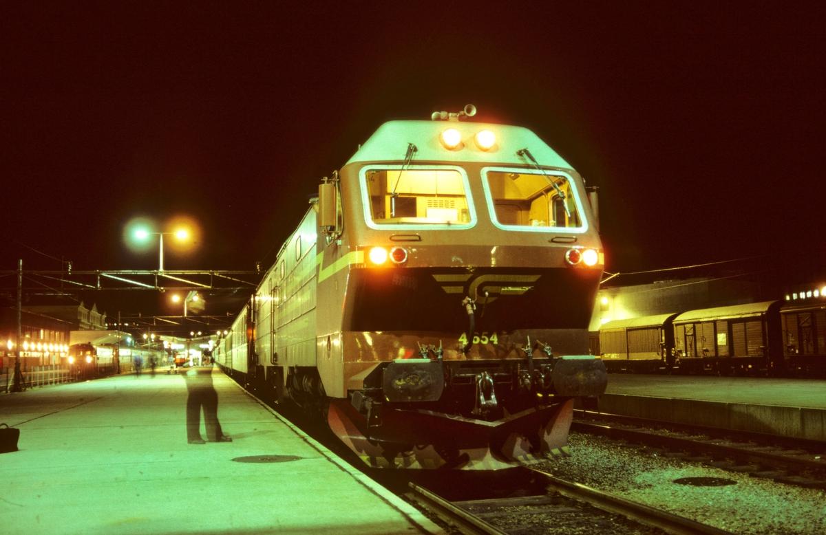 NSB nattog til Bodø på Trondheim stasjon, tog 455, med dieselelektrisk lokomotiv Di 4 654. Togføreren (overkonduktøren) overleverer bremselappen til lokomotivføreren.