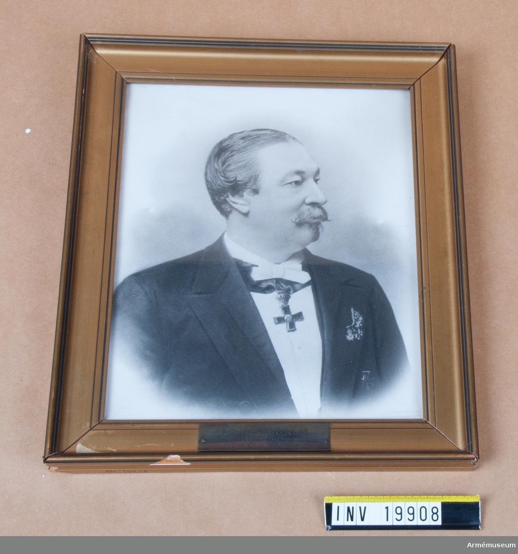 Fotografi i gul/grön träram föreställande byråchef (1885-05-22-1900-01-05) C L Thimgren. Thimgren bär Carl XIII:s halskors. Ramen lös i konstruktionen. Till vänster är 1 cm bortflagad bit av målningen i ramen. Tejpfläck. Samtliga hörn av ramens målning är kantstött.