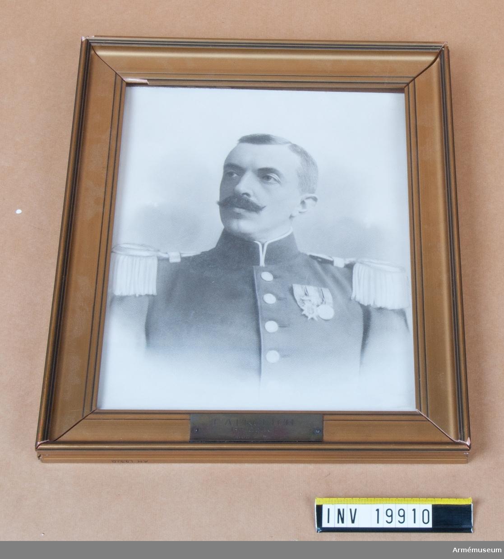 Fotografi i ram föreställande byråchef F.A. Frölich (1905-12-20-1915-04-10). Frölich bär uniform m/ä och två medaljer. Ramen hel.