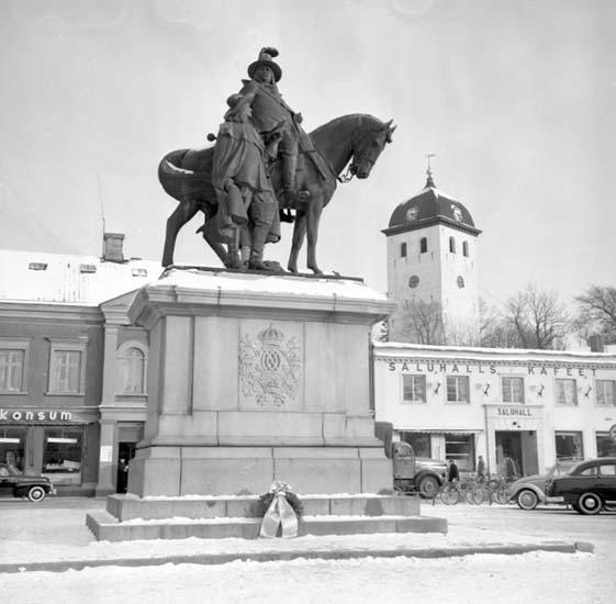 Krans lagd vid dubbelstatyns sockel på Kungstorget, Uddevalla, i februari 1958