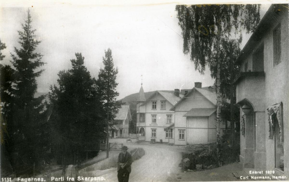 """Skarpsno- og Håvelsrud-bygningar fotografert frå vegen til Øystre Slidre. Mann på vegen i framgrunnen. Med handskrift: """"Heime"""""""
