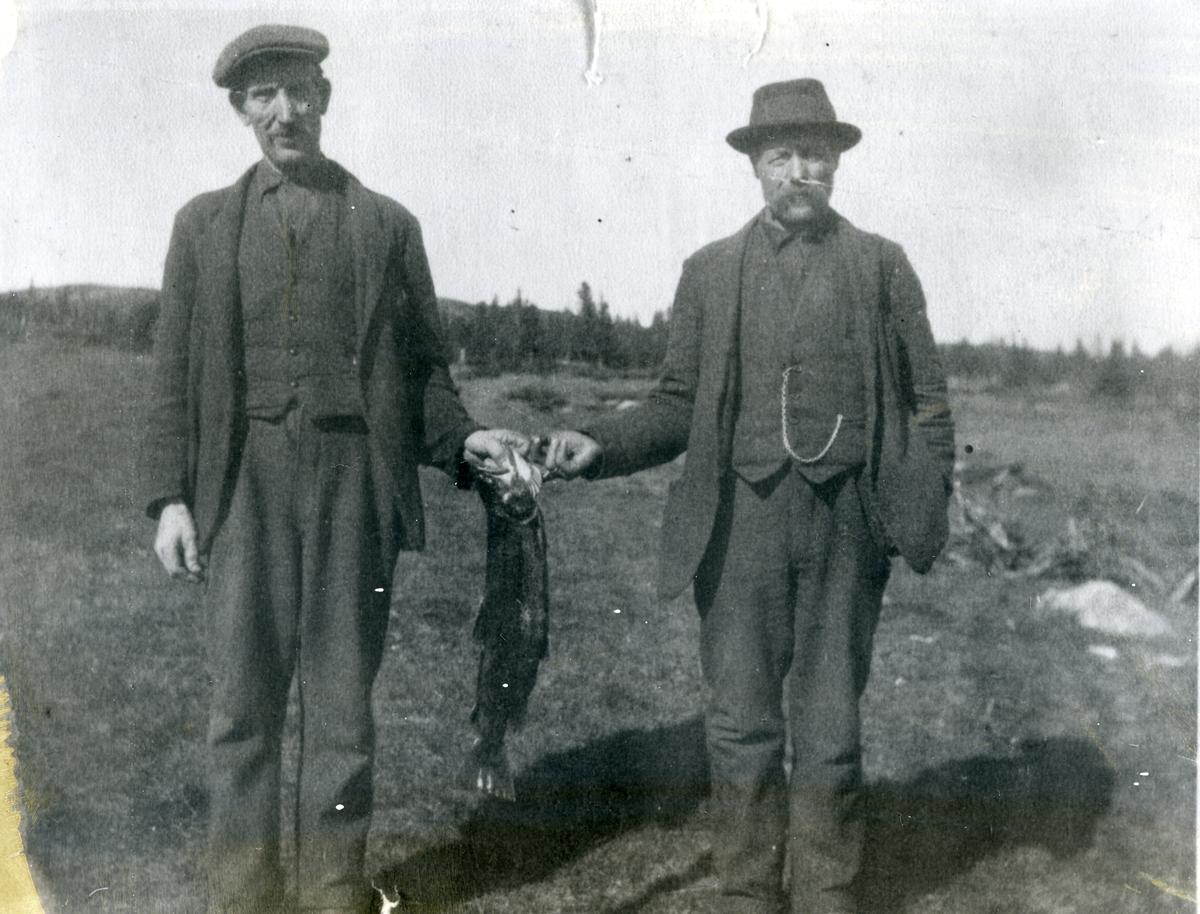 To menn med ein fisk imellom seg