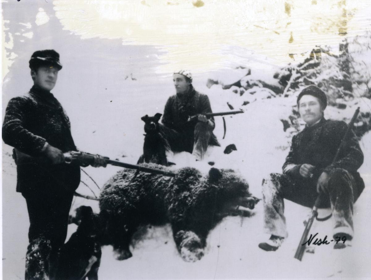 """3 jegere, """"Vøliskarene"""" (Vårum) sitter rundt ei binne de har skutt. Alle har våpen. To hunder er også med. Det er snø på bildet. Binne ble skutt like sør for Tingvang i Øystre Slidre. Fra venstre; Knut Vårum,Torleiv Moen og fotograf Li til høyre."""