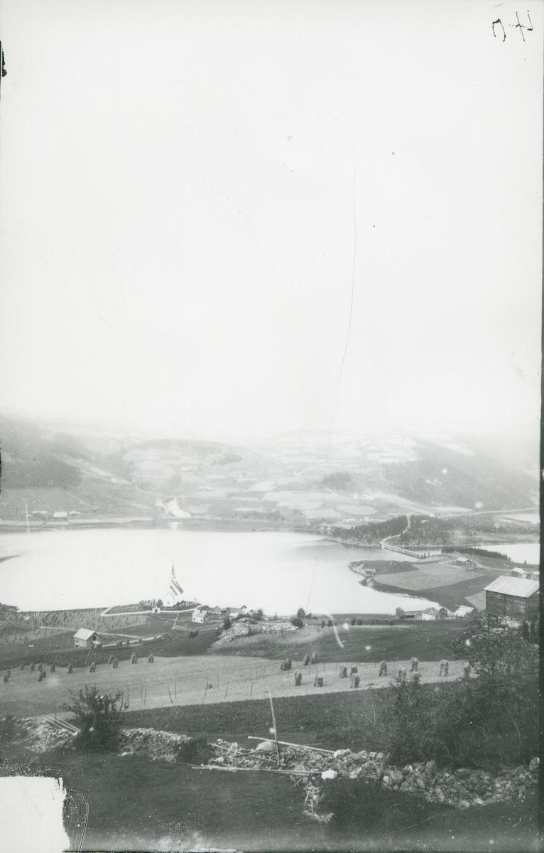 Ulnes, Nord-Aurdal. Mot vest. Ulneskyrkja nede ved Strandefjorden. Ulnesbrua og skolen helt til høyre. Sundheimselva midt i bildet med Steindegardene til venstre og Sundheimsgardene til høyre.