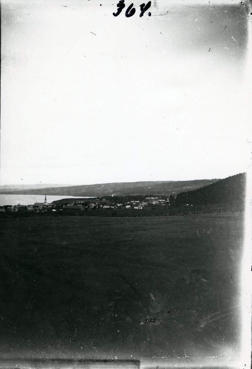 Landskapsbilde med jorder i forgrunnen, ei bygd med kirke midt i bildet, en innsjø til venstre og skogkledde åser rundt. Motivet antas å være fra området rundt Mjøsa.