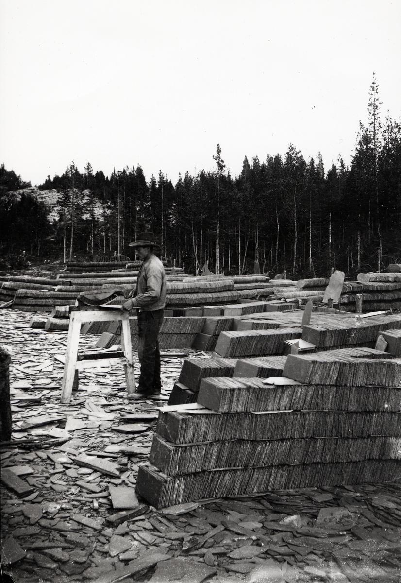 Valdres Skiferbrud. En mann klipper rektangulær skifer med Kollstadsaksa. Tatt rundt 1900.