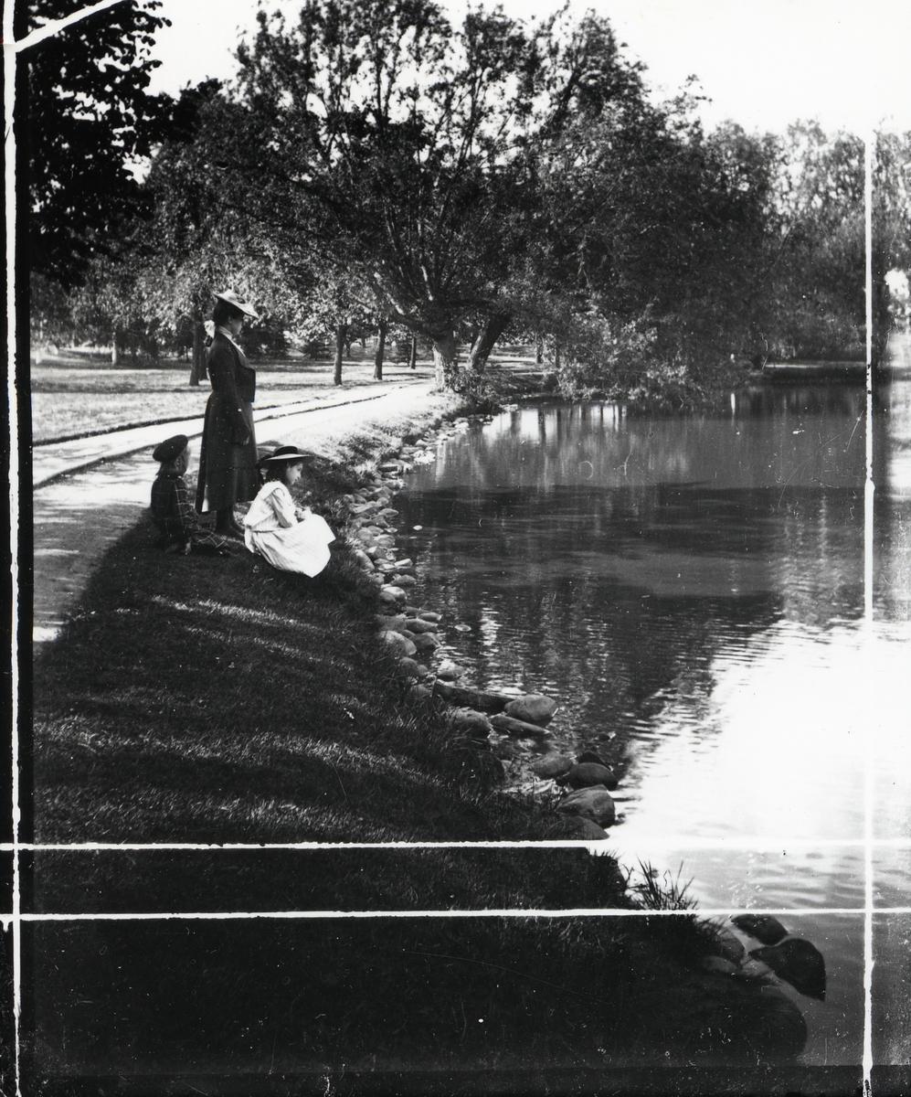 Kvinne og 2 barn ved et vann (innsjø)