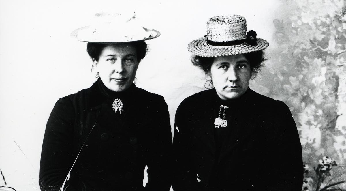Portrett av 2 kvinner. Begge iført mørke kjoler, sølje i halsen og stråhatt på hodet.