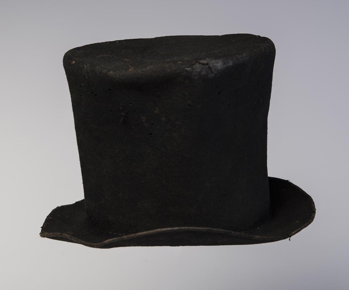 Filthatt med høy stiv pull som er flat på toppen.  Rundt ytterkanten av bremmen er det påsydd et smalt bånd. Hatten har svettebånd og 1/2 av høyden av hatten er fôret. Rester etter en skinn på undersiden av bremmen. Inne i pullen er det papir med tekst. Øvre del av hatten har større omkrets enn lenger nede. Denne type hatt er forløperen til flosshatt.