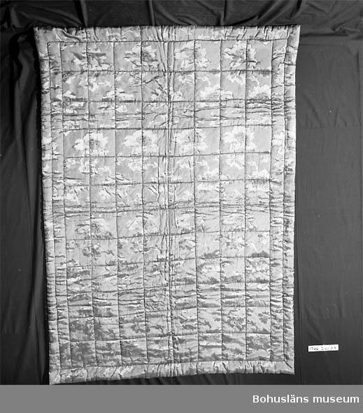 410 Mått/Vikt !L:210, B:145 CM 394 Landskap BOHUSLÄN Vinröd framsida av regnatfibrer med invävt växt/blom-mönster. Baksida av gul-beige bomull. Tillverkaren är inlämnarens svärmor. Hon var täckstickerska bosatt i Strömstad. Hon började tillverka handstickade sidentäcken på 1920-talet och fortsatte inpå 1950-talet. Hon lärde sig själv och fick ett bra ryckte som täckstickerska. UM24696 är ett likadant täcke.