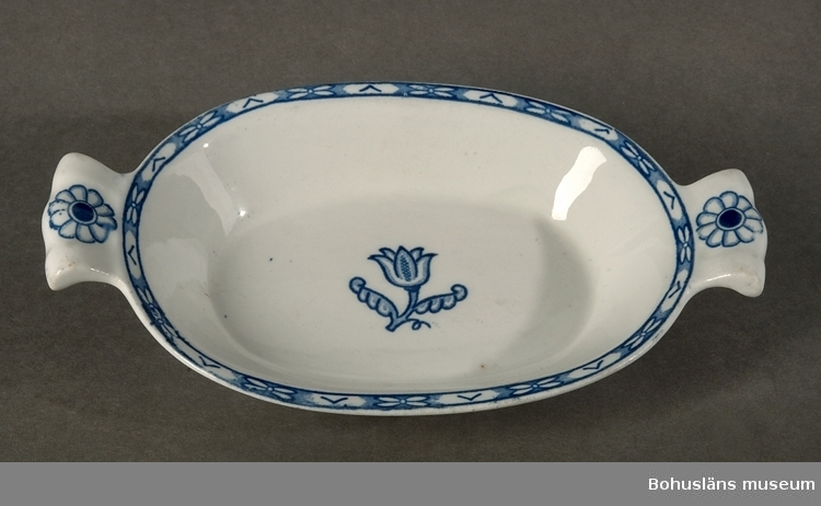 """Stiliserad blå kantdekor och tulpanliknande blomma i mitten. Ur servis """"Holland"""". Formgivare: Wilhelm Kåge."""