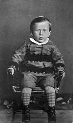 Studioportrett av liten gutt på en stol.