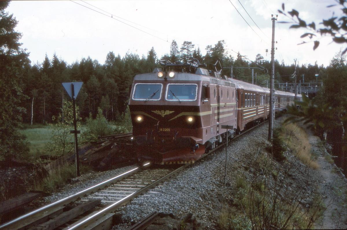 NSB ekspresstog 63 Oslo - Bergen med elektrisk lokomotiv El 16 2201 og vogner type 5 passerer Movatn.