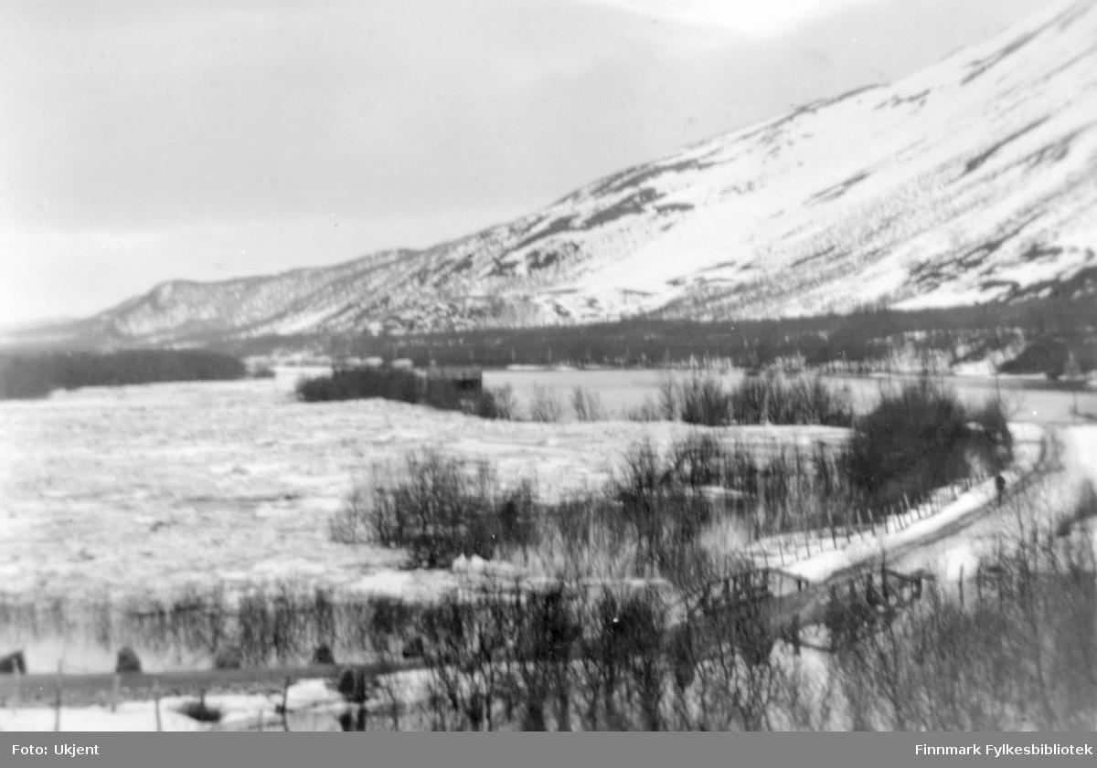 """Isgang i Tana. Bildet er tatt 23.05.1929. Bak bildet står det skrevet """"Kjosen og Skriverfjorda."""" Muligens Algasvarre til høyre med utsikt sørover. Bekken som brua krysser heter Sundijohka eller Fogdebekken.  Muligens fotografert under en storflom."""