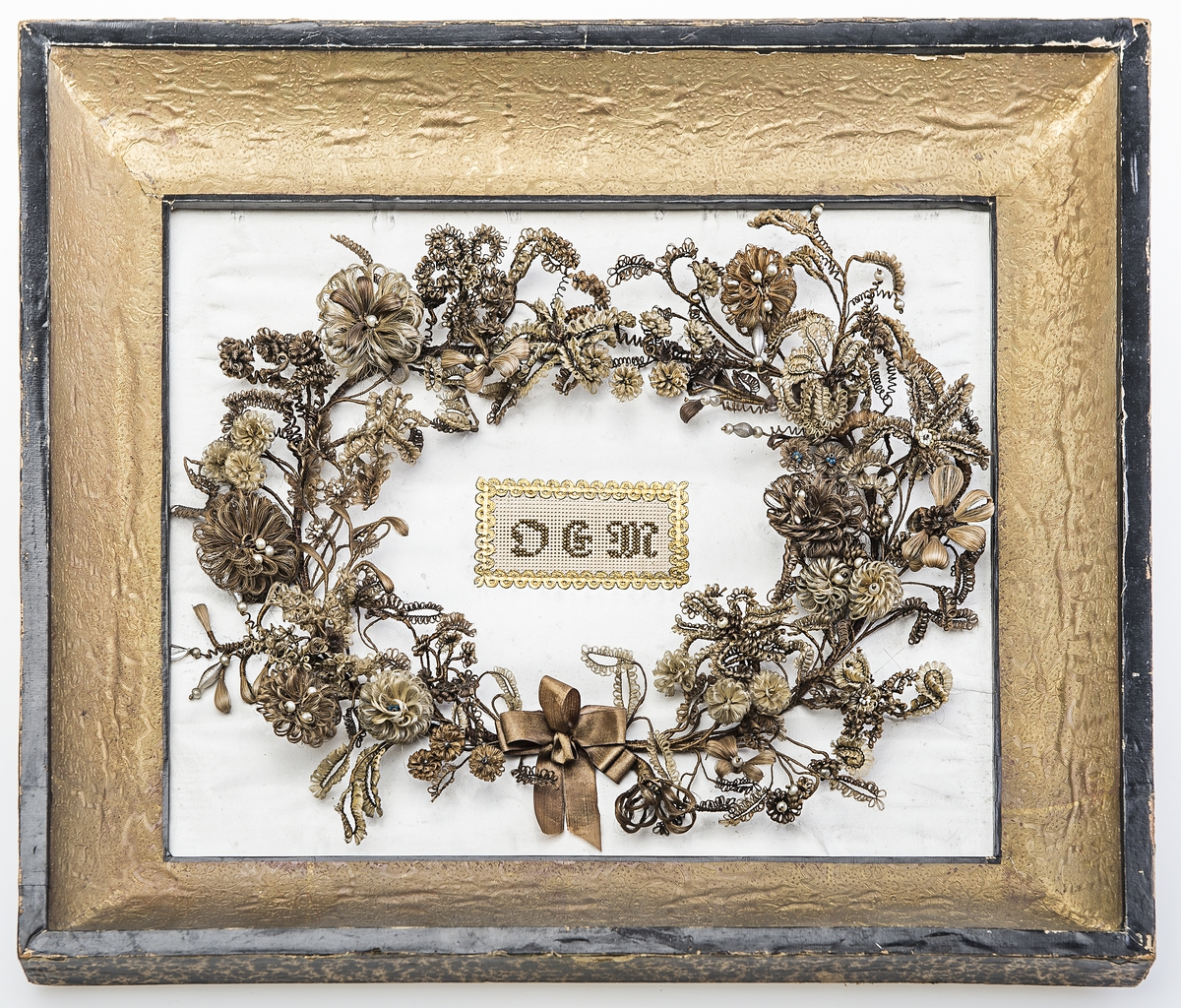 Et bilde som består av en krans av hårblomster i brune og blonde nyanser på hvit bunn. Blomstene er laget ved at de er tvinnet rundt tynn ståltråd. Stilkene er tykkere og tvinnet med hår. Turkis og perlemorsskinnende glassperler er brukt som dekor i blomsterhodene og ytterst på stenglene. Kransen er nede holdt sammen med  en brun silkesløyfe. Kransen ligger på hvit papirbunn. Midt i bildet er initialene OEM (Oline Elisabeth Moe) bordert i brune glassperler på stramei, og det er  en gullbord rundt initialene. Arbeidet er limt opp på en treplate. Rundt er det en treramme pålimt ullpapir og sort papir på forsiden, og melert sort og brunt papir på baksiden. Det er et sort bomullsbånd festet i metallhemper for oppheng.