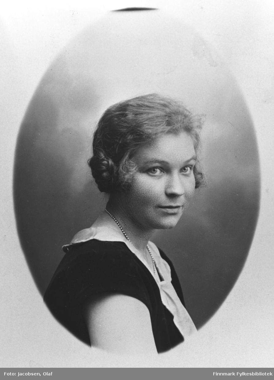 Halvkroppsportrett av en ung kvinne, Ågot Wara. Hun er kledd i en kortermed mørk kjole med hvit krage. Bildet er kopiert i ovalform.