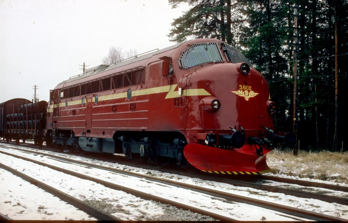 NSB dieselelektrisk lokomotiv Di 3 602 med godstog på Telneset. Dette lokomotivet var det første av totalt 35 dieselelektriske lokomotiver NSB kjøpte fra NOHAB i Trollhattan . Lisensprodusert fra GM-EMD division La Grange Illinois. Byggenr. 2246 hos NOHAB. Dieselmotor GM 567C-16. Her er lokomotivet nylig malt opp i den rødbrune fargesettingen med gul stripe. 602 var den siste av NOHAB'ene som ble malt slik.