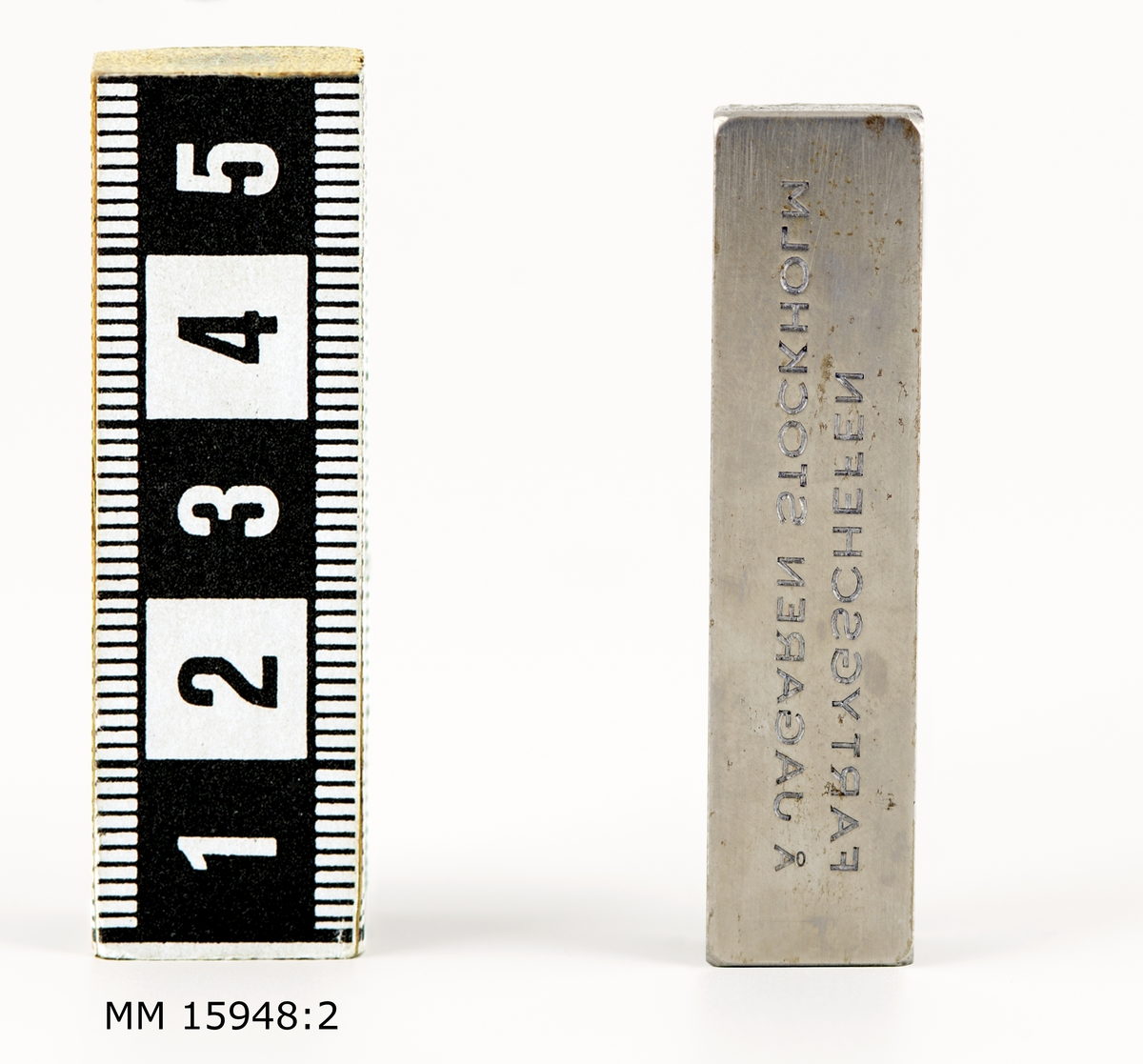 """Rektangulärt metallstycke vars bredsida är inristad med texten: """"FARTYGSCHEFEN Å JAGAREN STOCKHOLM"""". Texten ses spegelvänt för betraktaren. Ovansidans kanter fasade."""