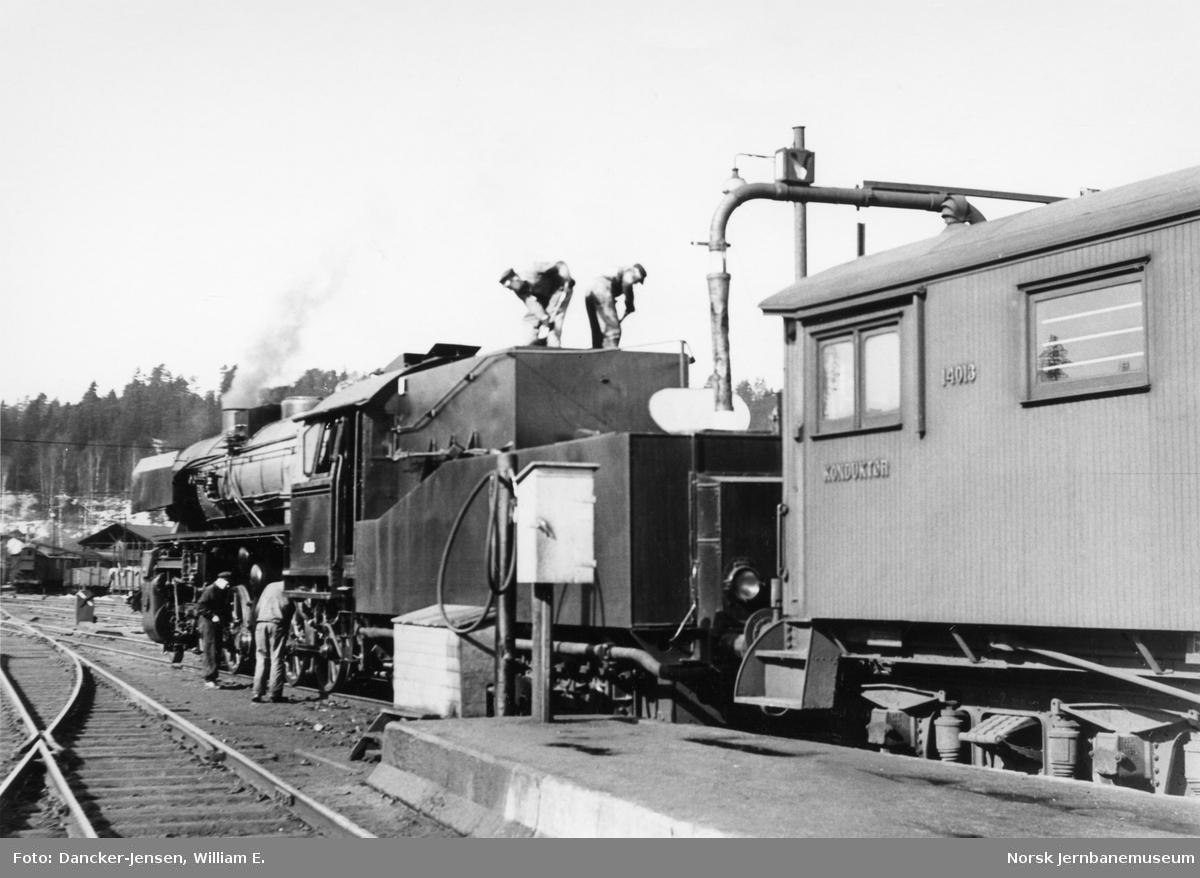 """Vannfylling på damplokomotiv type 63a med """"Kastentender"""" foran Bergenstoget"""