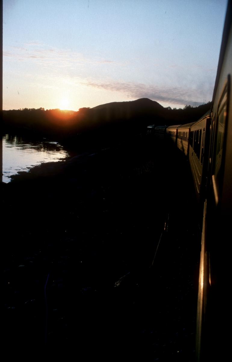 Tog 451 Trondheim - Bodø kjører inn i solnedgangen mellom Fauske og Bodø.