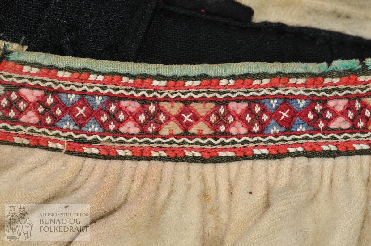 Kveitestakk. 7 høgder der dei 2 breidate framme er rettklipte, dei andre 5 er smalare og skråklipte. Saumen midt foran er handsydd, dei andre er sydd med maskin. Sauma av grov, lett valka, sauekvit ullkypert. Line av svært falma svart ull lerret. Påsydd løyesaum, kanta med lysare grøn ull lerret. Upplut i same tøy som stakken. Påsydd svart valka ull lerret med løyesaum. Faslar av svart ullkypert med maskinstikningar langs kantane. Trådhempe av ullgarn til hekting i knappar framme på lina.