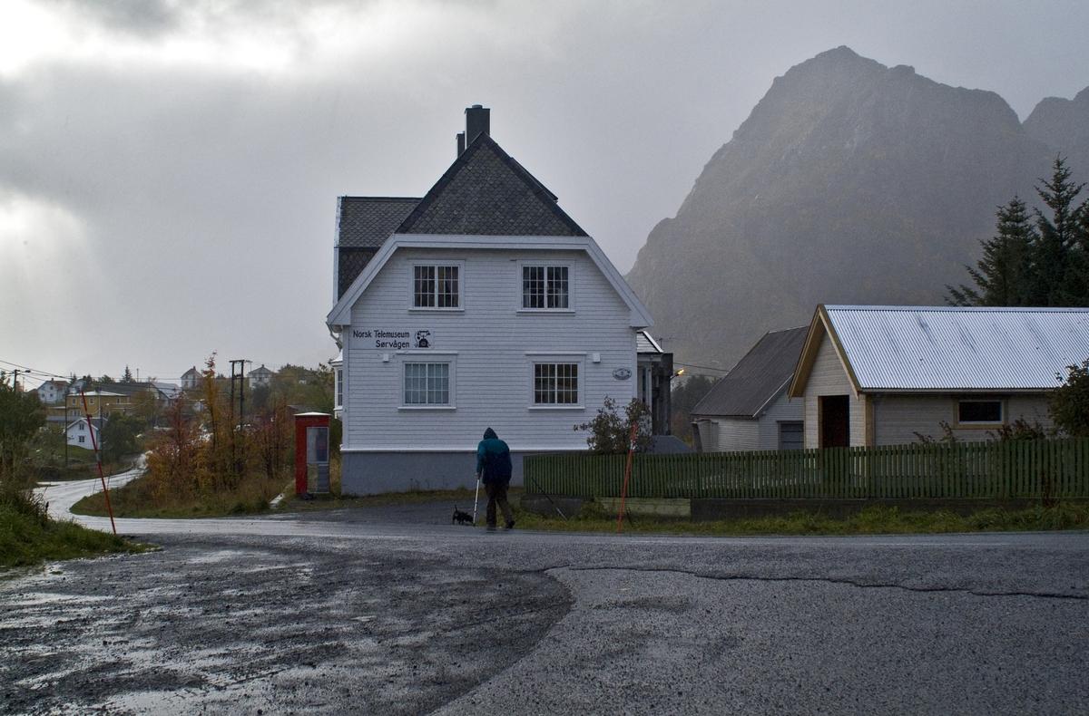 Denne telefonkiosken står ved det gamle telebygget i Sørvågen, og er en av de 100 vernede kioskene i Norge. De røde telefonkioskene ble laget av hovedverkstedet til Telenor (Telegrafverket, Televerket). Målene er så å si uforandret.  Vi har dessverre ikke hatt kapasitet til å gjøre grundige mål av hver enkelt kiosk som er vernet.  Blant annet er vekten og høyden på døra endret fra tegningene til hovedverkstedet fra 1933. Målene fra 1933 var: Høyde 2500 mm + sokkel på ca 70 mm Grunnflate 1000x1000 mm. Vekt 850 kg. Mange av oss har minner knyttet til den lille røde bygningen. Historien om telefonkiosken er på mange måter historien om oss.  Derfor ble 100 av de røde telefonkioskene rundt om i landet vernet i 1997. Dette er en av dem.