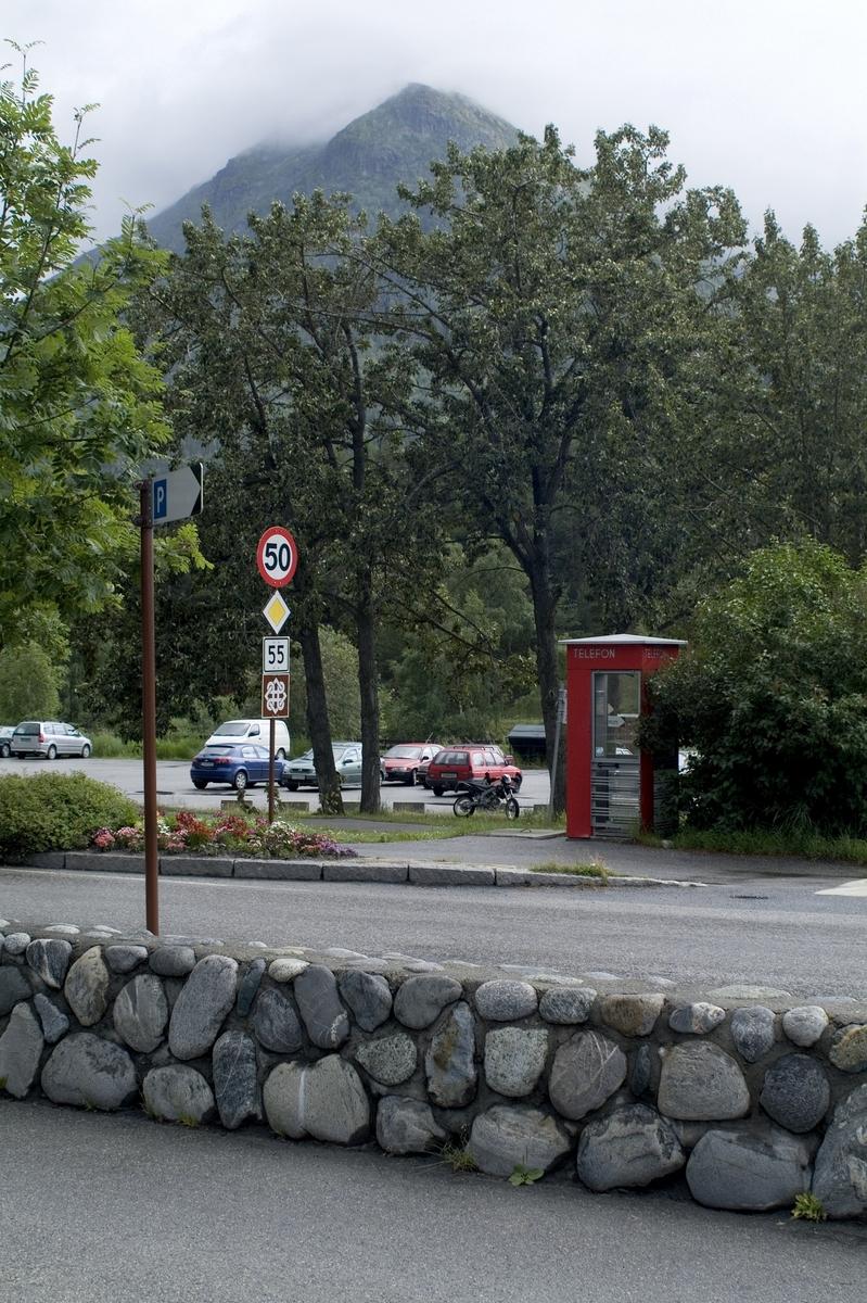 Telefonkiosken står ved postkontoret i Lom, og er en av de 100 vernede telefonkioskene i Norge. De røde telefonkioskene ble laget av hovedverkstedet til Telenor (Telegrafverket, Televerket). Målene er så å si uforandret.  Vi har dessverre ikke hatt kapasitet til å gjøre grundige mål av hver enkelt kiosk som er vernet.  Blant annet er vekten og høyden på døra endret fra tegningene til hovedverkstedet fra 1933. Målene fra 1933 var: Høyde 2500 mm + sokkel på ca 70 mm Grunnflate 1000x1000 mm. Vekt 850 kg. Mange av oss har minner knyttet til den lille røde bygningen. Historien om telefonkiosken er på mange måter historien om oss.  Derfor ble 100 av de røde telefonkioskene rundt om i landet vernet i 1997. Dette er en av dem.