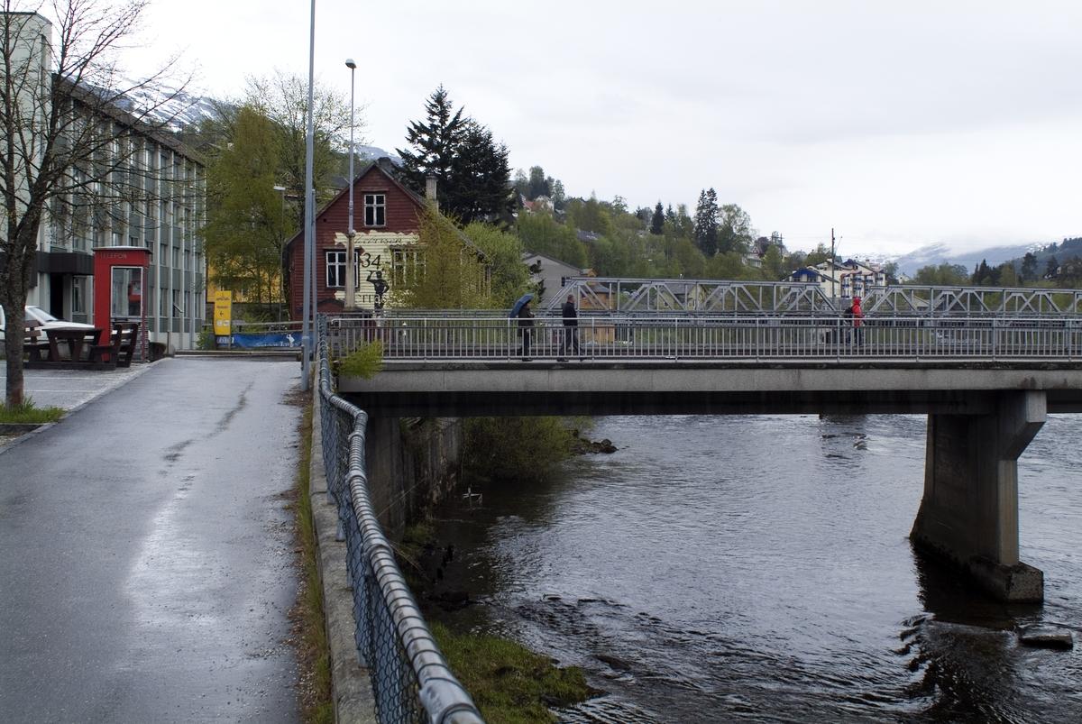 Denne telefonkiosken står i Hardangervegen 1, Voss, og er en av 100 vernede telefonkiosker i Norge. De røde telefonkioskene ble laget av hovedverkstedet til Telenor (Telegrafverket, Televerket). Målene er så å si uforandret.  Vi har dessverre ikke hatt kapasitet til å gjøre grundige mål av hver enkelt kiosk som er vernet.  Blant annet er vekten og høyden på døra endret fra tegningene til hovedverkstedet fra 1933. Målene fra 1933 var: Høyde 2500 mm + sokkel på ca 70 mm Grunnflate 1000x1000 mm. Vekt 850 kg. Mange av oss har minner knyttet til den lille røde bygningen. Historien om telefonkiosken er på mange måter historien om oss.  Derfor ble 100 av de røde telefonkioskene rundt om i landet vernet i 1997. Dette er en av dem.