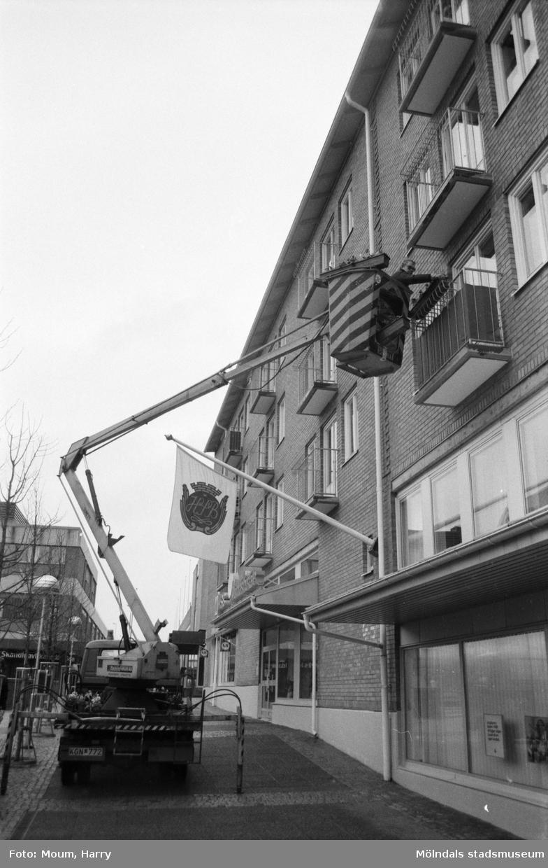 Uppsättning av blomlådor på hus vid Mölndals Torg med hjälp av kranbil, år 1985.  Fotografi taget av Harry Moum, HUM, Mölndals-Posten.