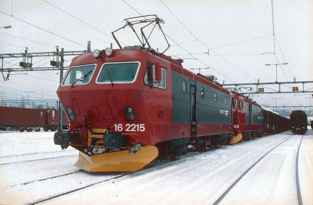 NSB godstog 5511 (Søndagstog Alnabru - Bergen) på Alnabru skiftestasjon med to lokomotiver type El 16. NSB hadde nylig begynt å male om lokomotivene etter et nytt designprogram i rødt, rødsort og gult.