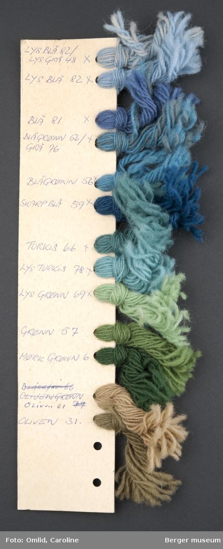 Pappremse med hull på en side, der garnprøver i forskjellige farger er knyttet på. Garnfargene er nummerert med blå kulepenn på kartongen.