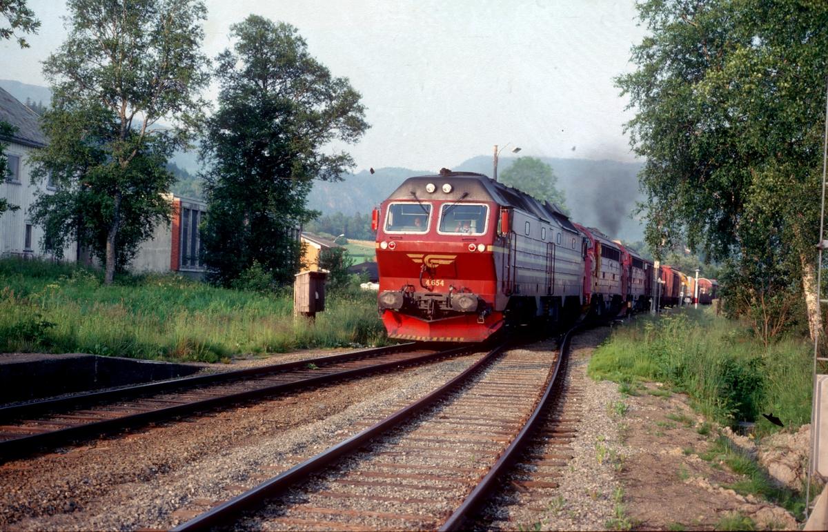 """Godstog 5793 til Bodø med tre dieselelektriske lokomotiver i fellesstyring (multippel), type Di 4 og Di 3, i trinn 8 gjennom Skatval stasjon. For å spare lokomotivpersonalet for støy er Di 4-loket lagt som """"styrevogn""""."""