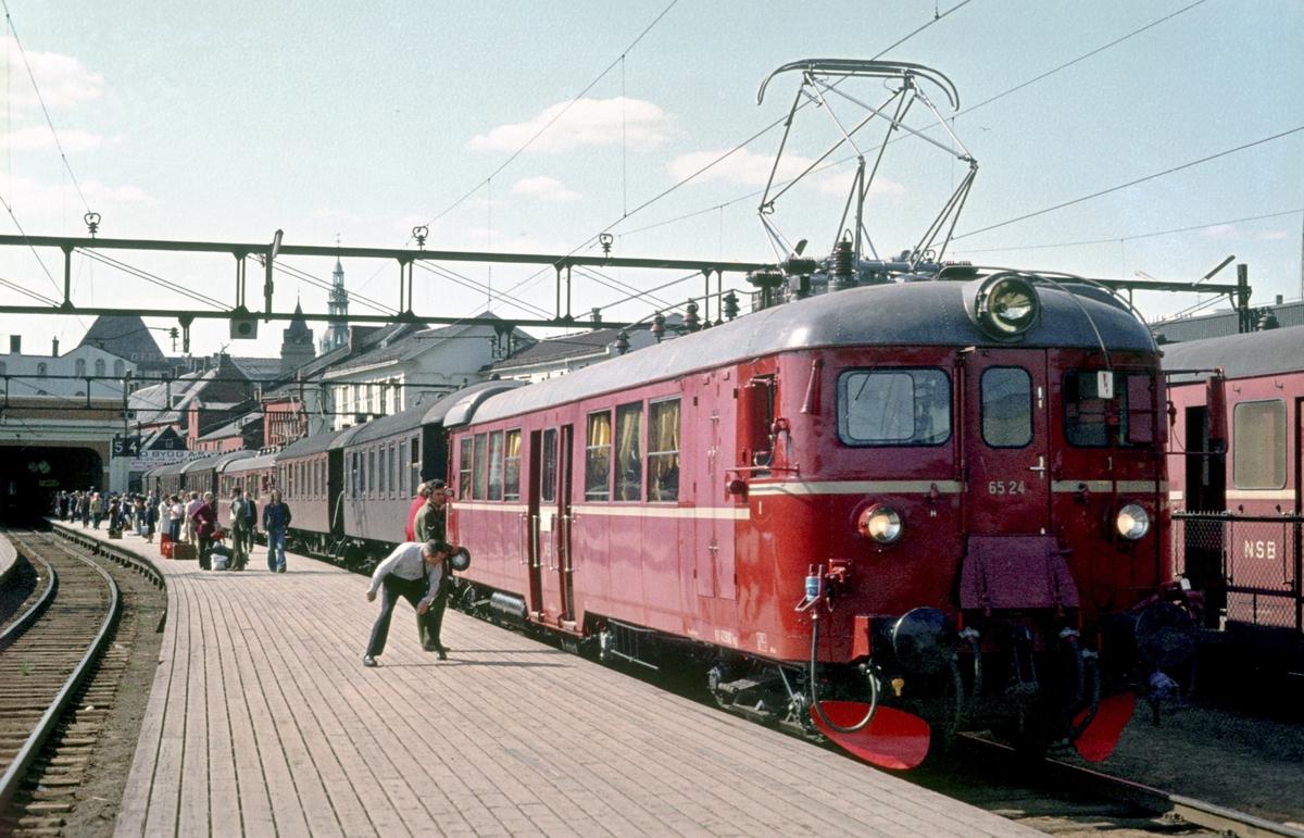 Persontog til Årnes og Eidsvoll med motorvognsett type 65 står klar på Oslo Ø. Toget ble delt i Lillestrøm. Lokomotivfører kontrollerer slaglengden.