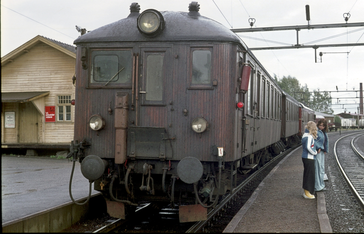 """Persontog til Årnes på Sørumsand stasjon. Venter på kryssende tog. Reisende står på mellomplattformen. Motorvognsett type 65, med motorvogn type 65A og trevogner. Styrevogn BFS 65 """"Ubåt""""."""