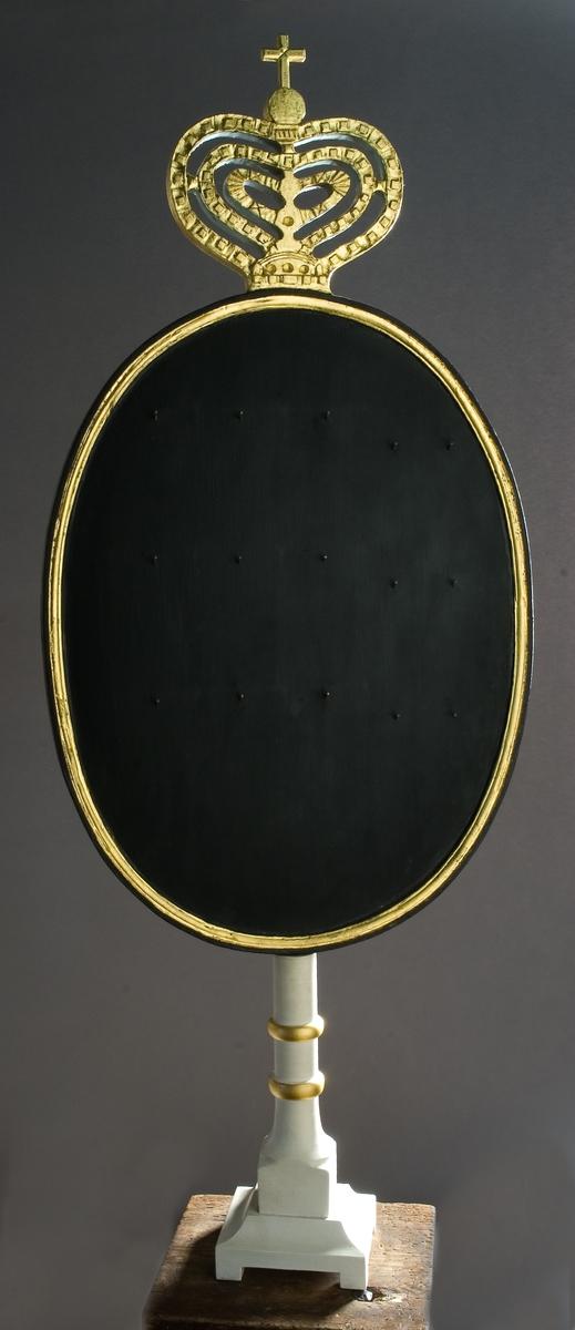 Nummertavla av trä. Kvadratisk fot, svarvat ben och oval nummertavla. Avslutas upptill med genombrutet hjärtformat ornament. Målat i vitt, guld och svart. 15 spikar för upphängning av siffror som anger vilken psalm som ska sjungas.