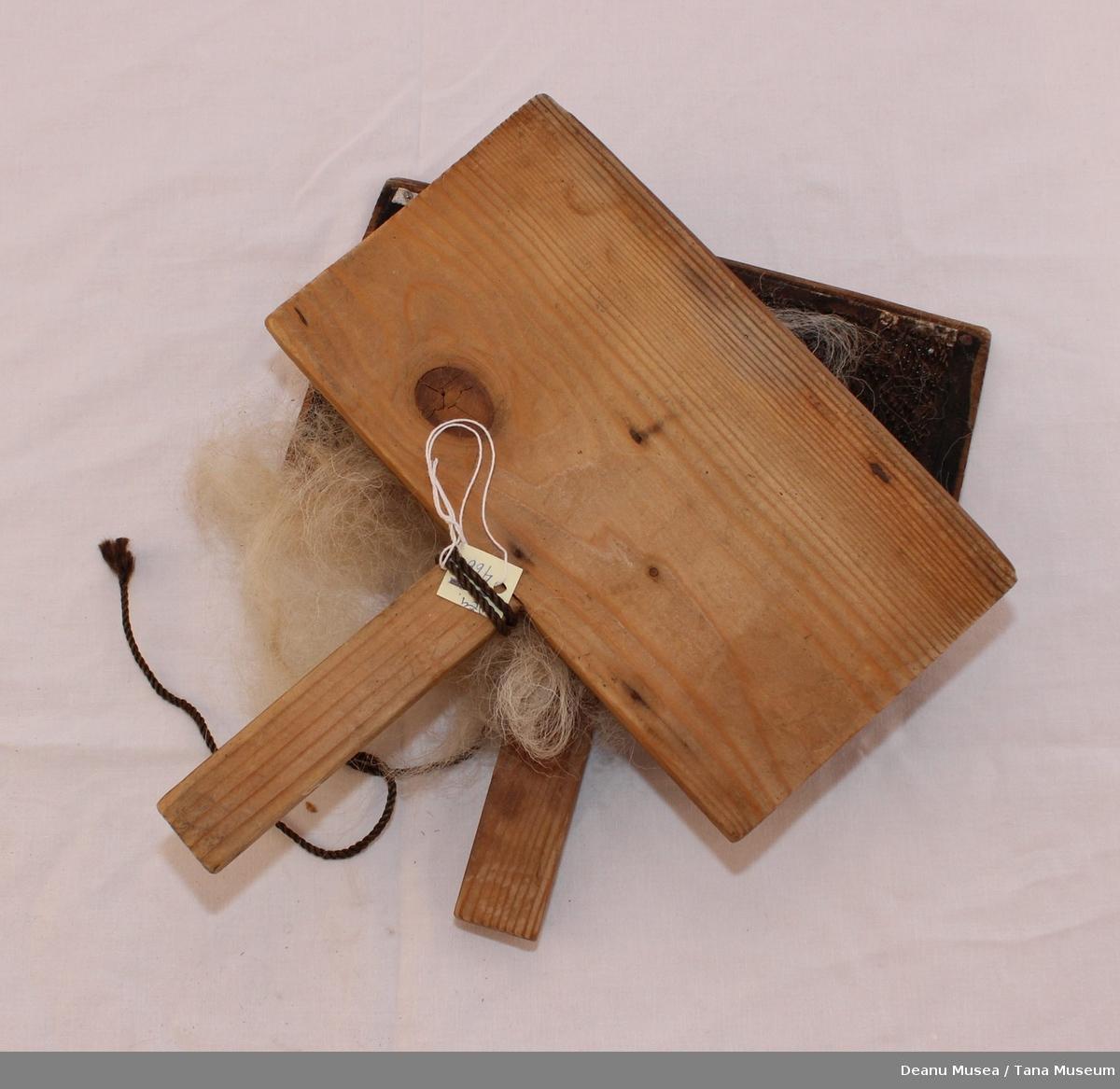 Ullkarder i tre. Kardene holdes sammen av brun syntetisk snor. Saueull i mellom kardene.