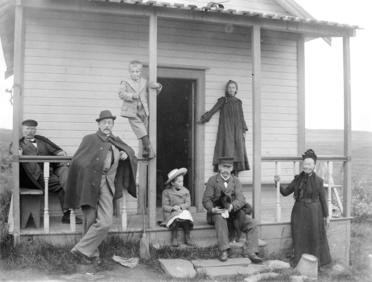 Her poserer en gruppe mennesker foran det som antas å være Gundersens hytte ved Vadsø (se referansebilde 01009- 016). Mannen som er kledd i en poncho og som lener seg mot gelenderet til innganen er Eilert Nikolai Brodtkorb. Mannen sittende til venstre for ham kan muligens være Rie Gundersen. Han har en sløyfe rundt halsen og sitter på en benk. Resten er ukjente. En liten jente og en mann sitter på trappen foran innganen. Mannen holder en hund i fanget. Det står en eldre kvinne til høyre for ham. Hun er kledd i kjole og hatt. En liten gutt balanserer på gelenderet bak Eilert. Gutten er kledd i jakke, knebukser, sokker, skjorte og sko. På bakken foran gutten kan man se en kost.