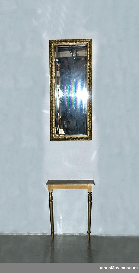 Rektangulär spegel med kantslipat glas med kvicksilverbeläggning på baksidan, använd hos Strands Mode.  Ramad med sju cm bred träram med rikt guldbronserad gipsbeläggning med rik dekor av akantusranka, lagerrand samt pärlstavar och lister. Använd tillsammans med spegelbord UM025944.  Skador på ramen. Åtgärdat 2003 - se Vårdrapport.