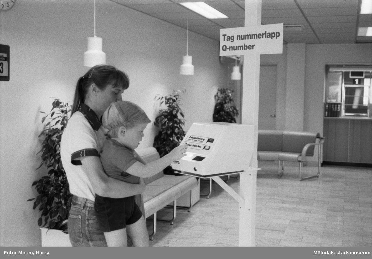 """Nyrenoverade postkontoret på Jungfruplatsen i Mölndal, år 1985. """"Joel Ringberg, 3 år får hjälp av mamma Majvor med att testa det elektroniska kösystemet.""""  För mer information om bilden se under tilläggsinformation."""