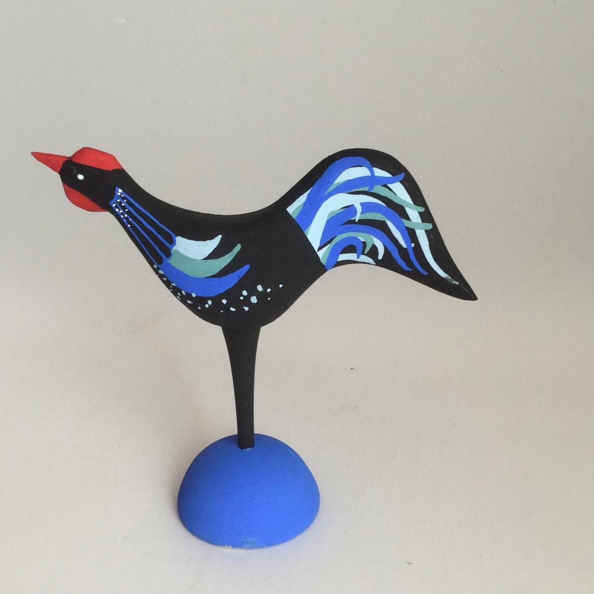 Prydnaden föreställer en tupp.Tuppen är täljd men har en fot som är svarvad.Foten är blå, kroppen är svart i grundfärgen med blå dekoration på. Näbb och kam i rött.Höjden är 120 och bredden är 115 mm.
