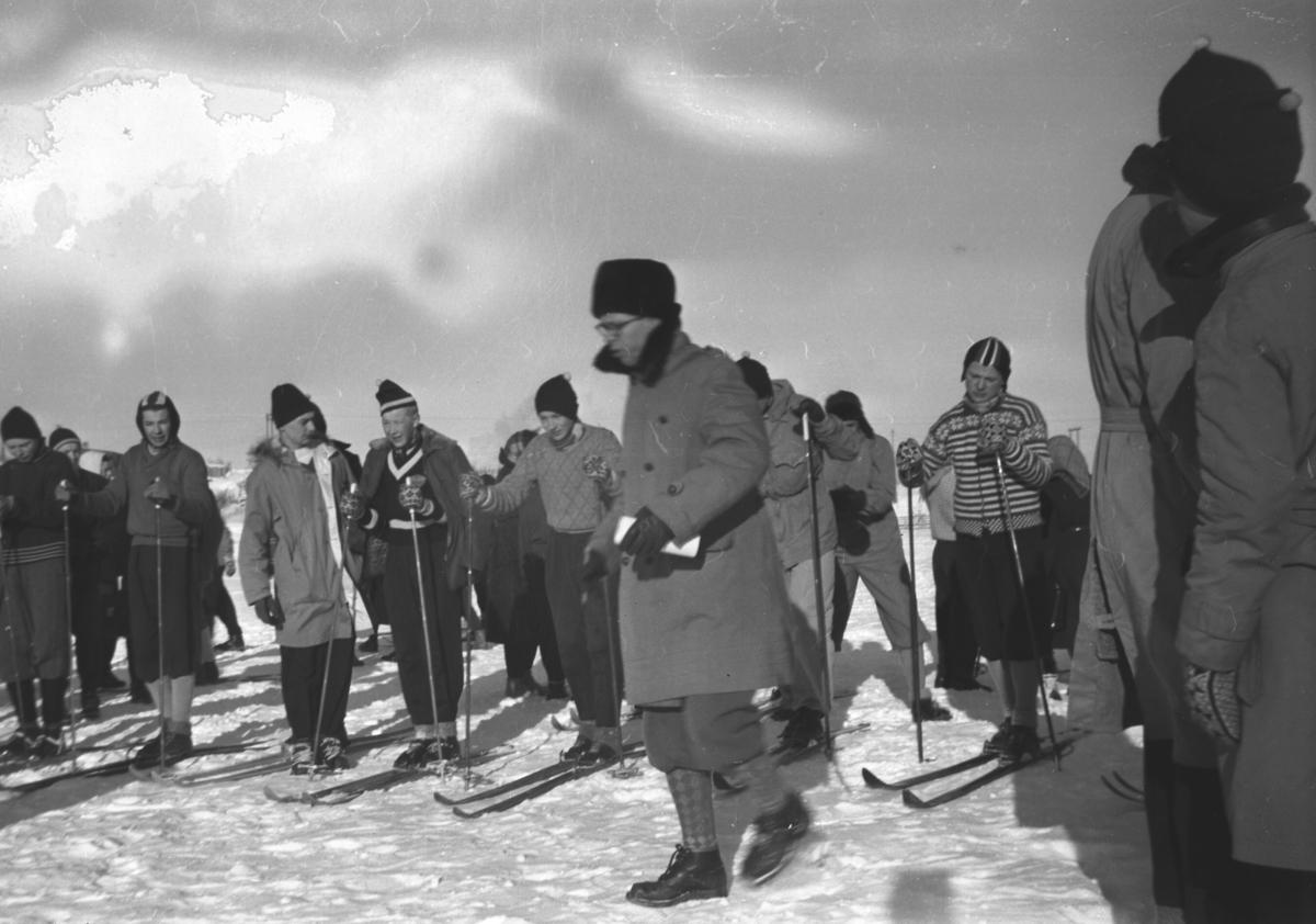 Bildet er antagelig fra et skistevne i Kirkenes., arrangert av realskolene i Øst-Finnmark, og viser personer i vinterklær og flere av dem har ski på beina. I midten foran står Knut Joki og litt bak han i stripet genser står Odd Ivar Hoftaniska.