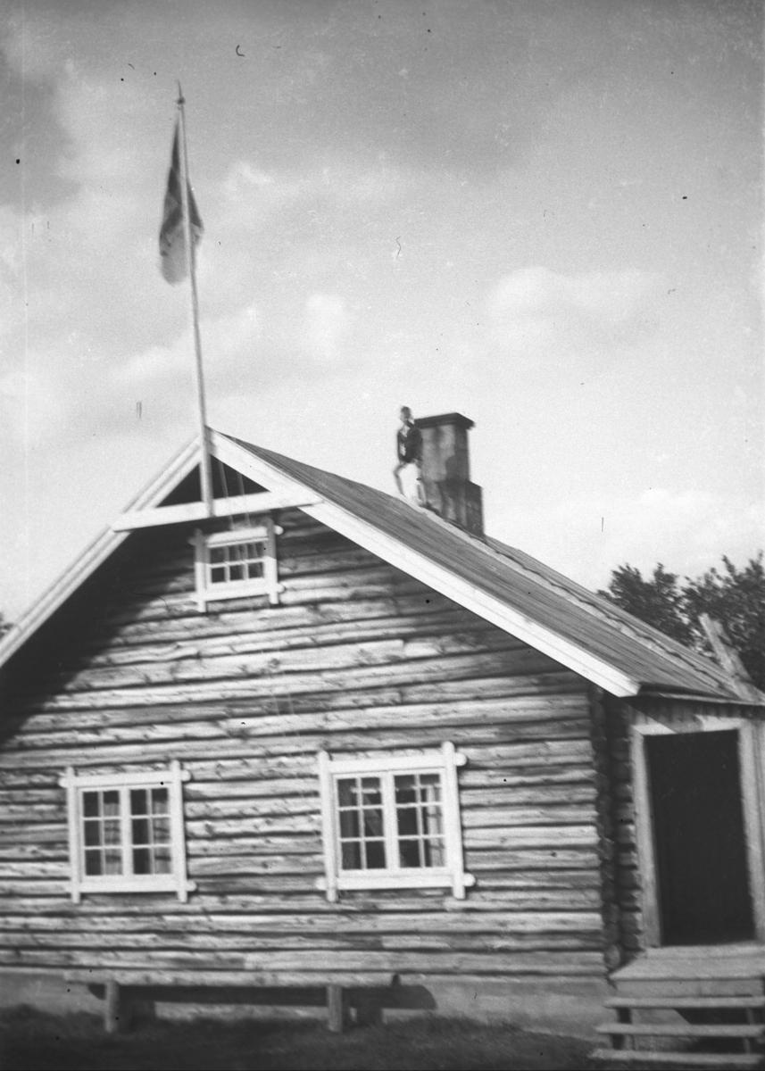 Tor Hauge står på taket til Alleknjarg fjellstue.