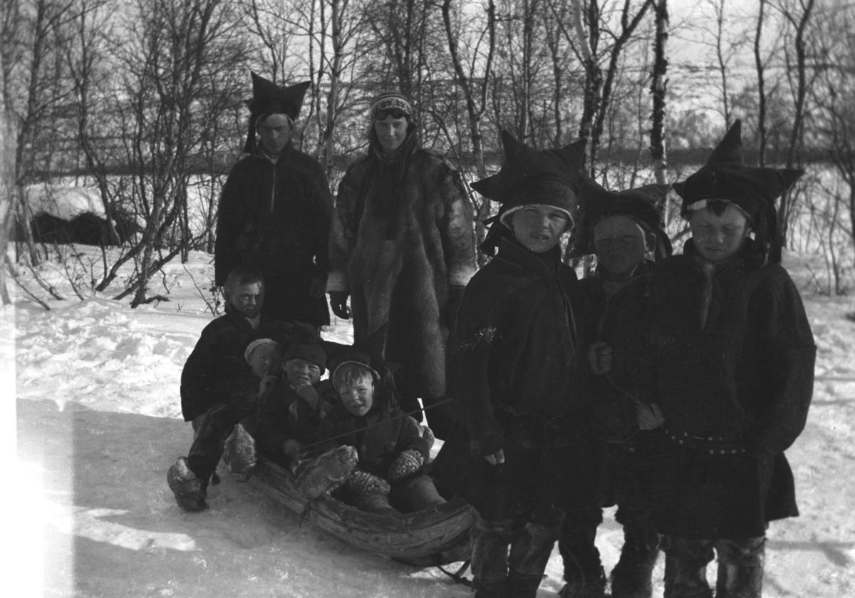 Ni personer fotografert en vinterdag i Alleknjarg. Gutten som sitter fremst i pulken er Tor Hauge og rett bak han står Frida Hauge. Resten er ukjent.