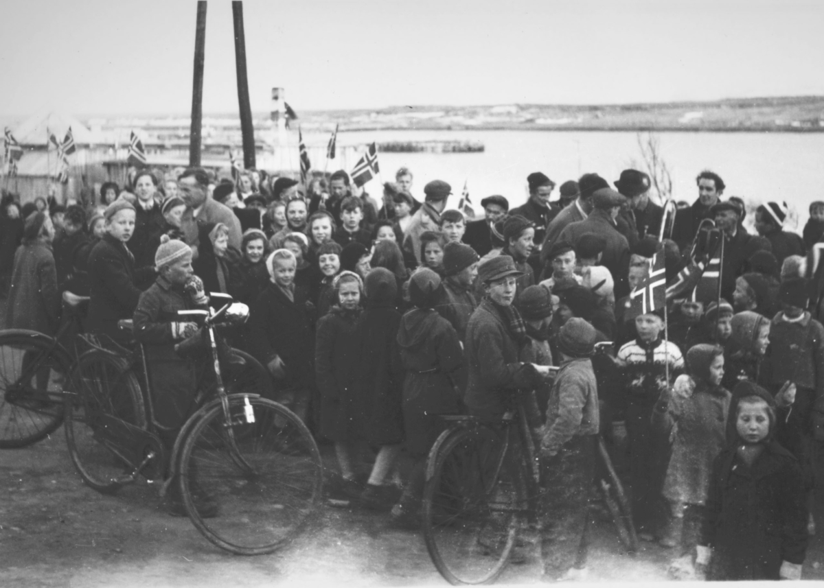 8.mai 1945 i Vadsø. En gruppe barn og voksne. De har pynta og har norske flagg.
