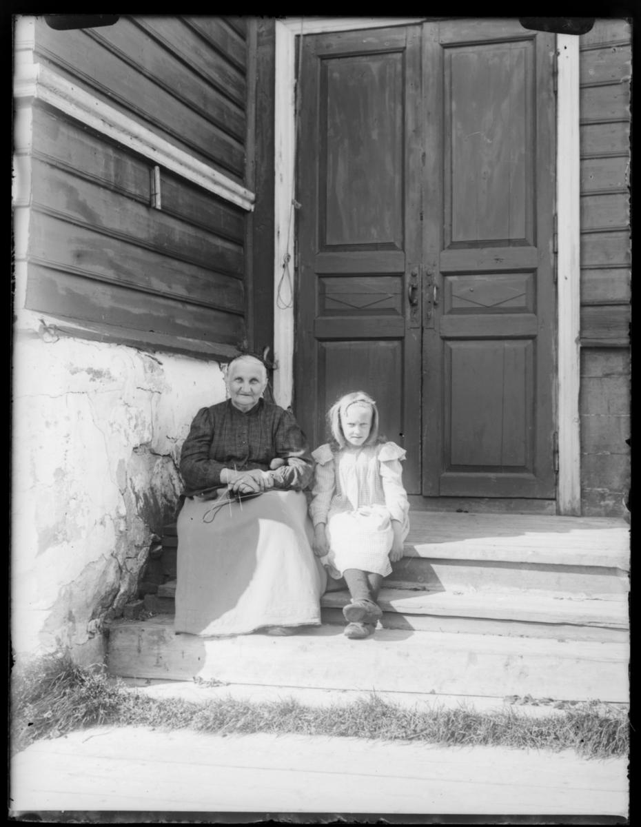 Boris Gleb, en eldre kvinne og ei ung jente sitter på trappa til en større bygning, antakelig kirka. Kvinnen har et strikketøy i hendene