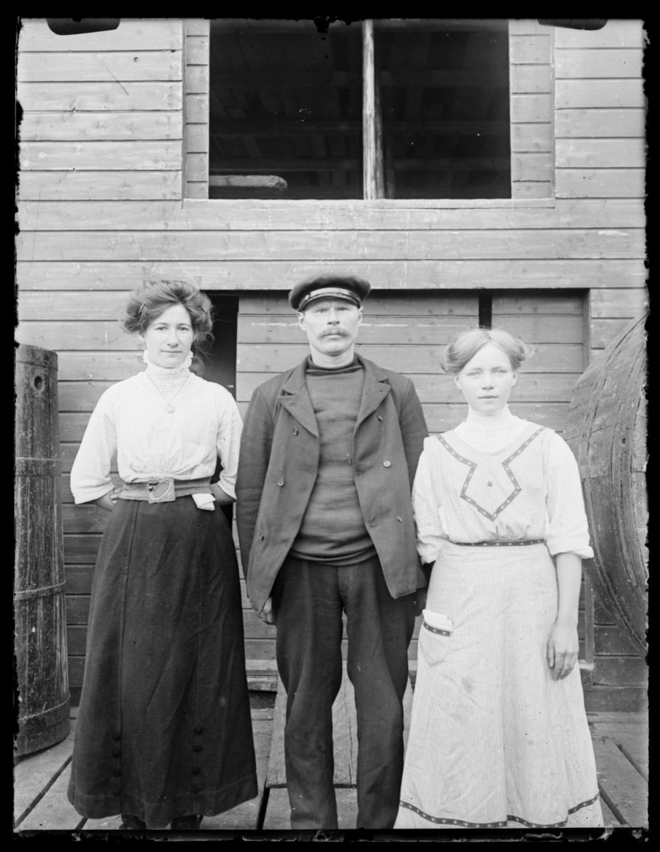 Portretter fra Makkaur. Mannen i midten er Ole Andreasen og kvinnen til høyre er Paulina Hansen. Vi vet ikke hva heter kvinnen til venstre. Mannen er kledt i båtslue, jakke, genser og bukse. Han har bart. Kvinnene finner vi også på andre bilder. Den ene i hvit bluse, svart skjørt og belte. Den andre i forkle lignende kjole. Begge har oppsatt hår