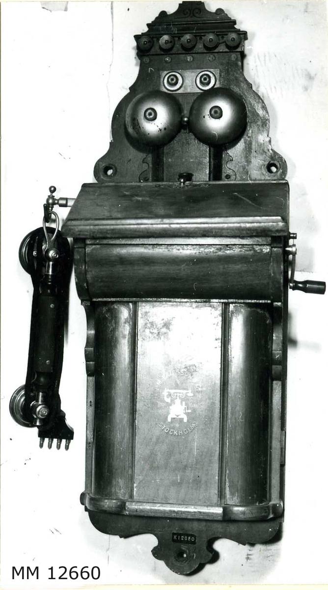 """Väggtelefon m/1895. Se även foto på MM 8252. Apparaten är innesluten i en kåpa av mahogny. Klyka för handmikrotelefonen placerad  på vänster sida av apparaten. Märkning överst: """"L.M. Ericsson & Co Patent Stockholm"""". På batterilocket: Firmamärke som utgöres av en bild, föreställande en bordstelefon samt testen: """"Trade Mark"""". Kring bilden: """"L.M. Ericsson & Co Stockholm"""". Märkning innanför locket: """"384585"""". Handmikrotelefonen märkt: """"Telefonaktiebolaget L M Ericsson, Stockholm, Sweden"""".  (Firmans namn ombildades år 1896 till Allmänna Telefon AB L.M. Ericsson)."""